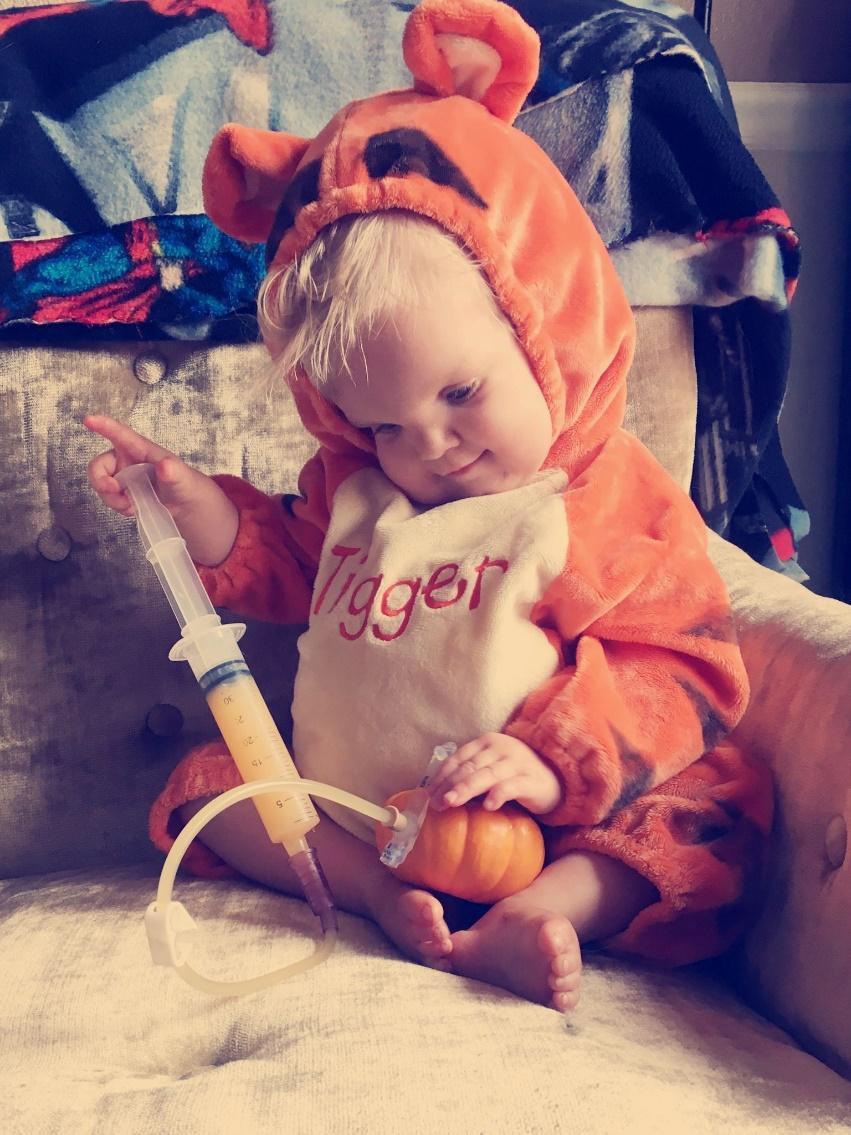 tube fed child feeding themselves with syringe