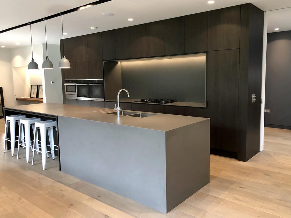 Contemporary kitchen dark walnut with grey stone island in Surrey