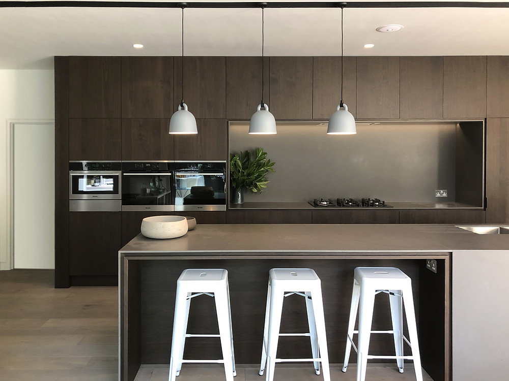 Contemporary walnut kitchen architecture with stone island in Haslemere, Surrey