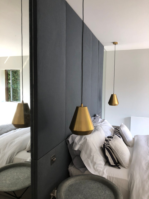 Modern Haslemere bedroom with gold pendants & fabric panels
