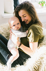 woman-in-green-shirt-holding-baby-while-