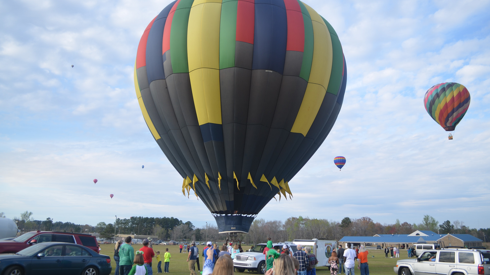 Airborne hot air balloons dot the sky as another (at center) prepares to launch from Southern Pines Regional Park at the 2018 Irish Balloon Fest, a major event in the annual Dublin-Laurens Saint Patrick's Festival.