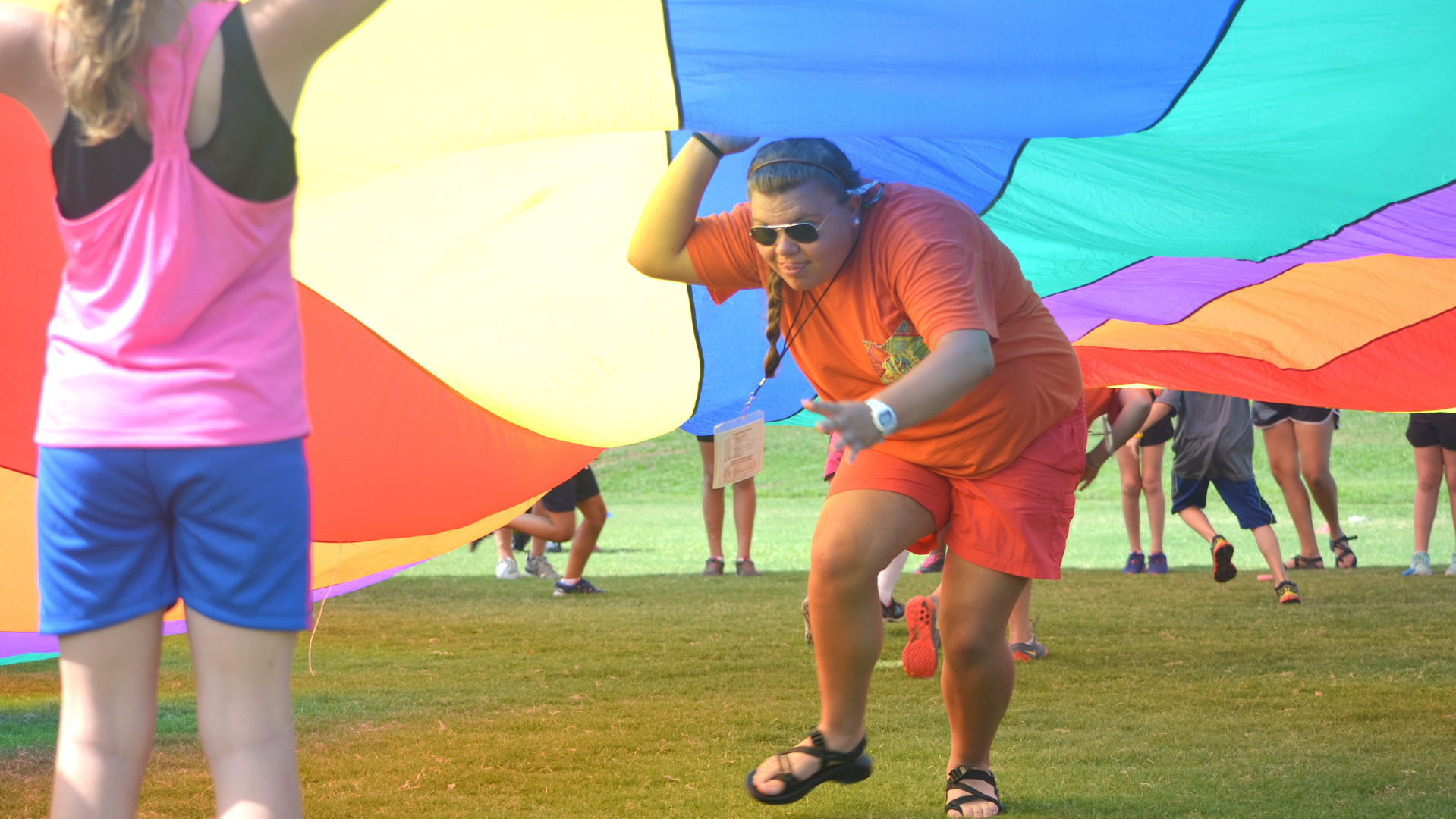 A camper runs underneath a parachute during an outdoor recreation game at a summer day camp in 2015.