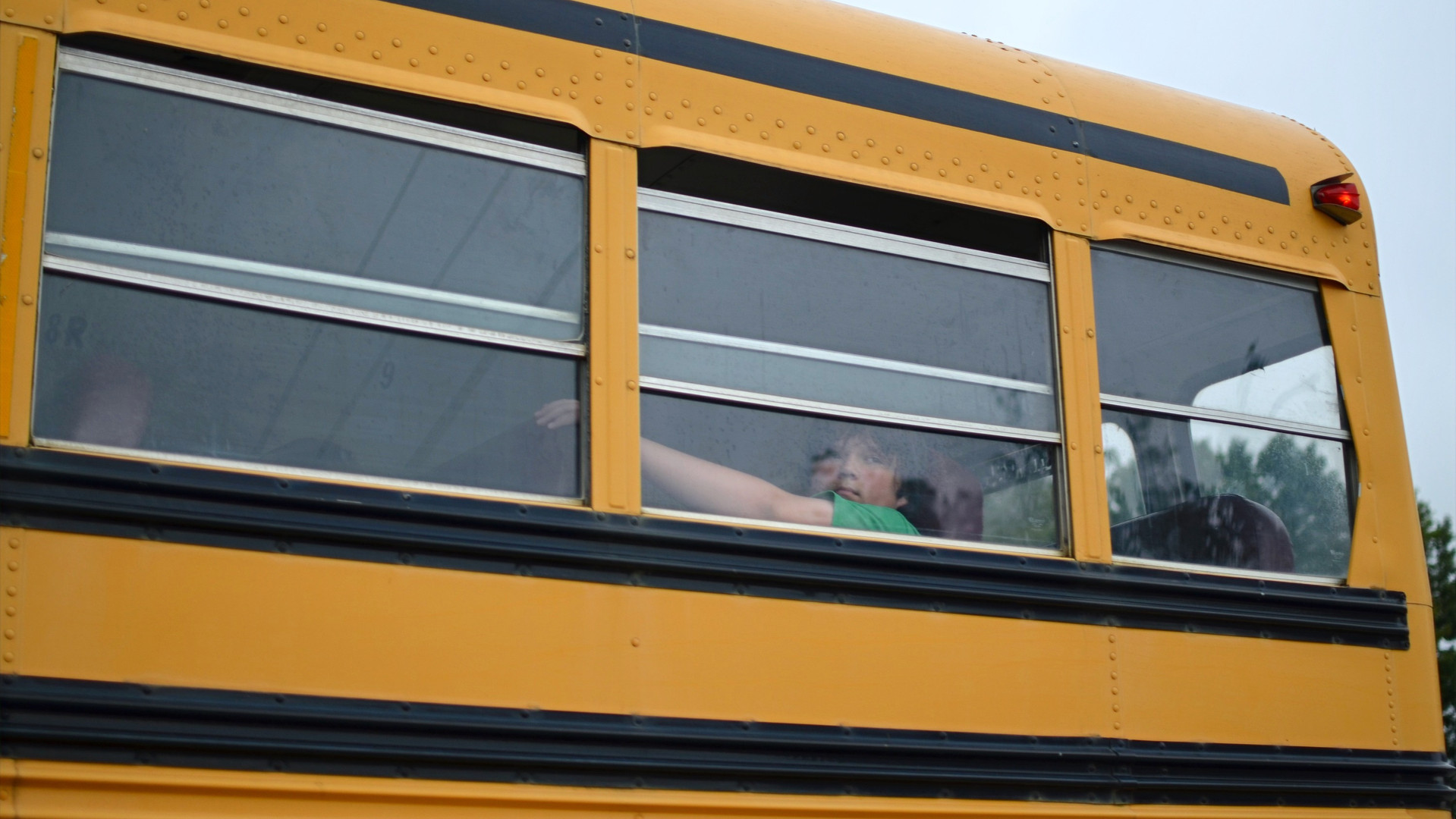 A middle school student gazes out the window of a school bus en route to campus on the first day of the 2015 school year.