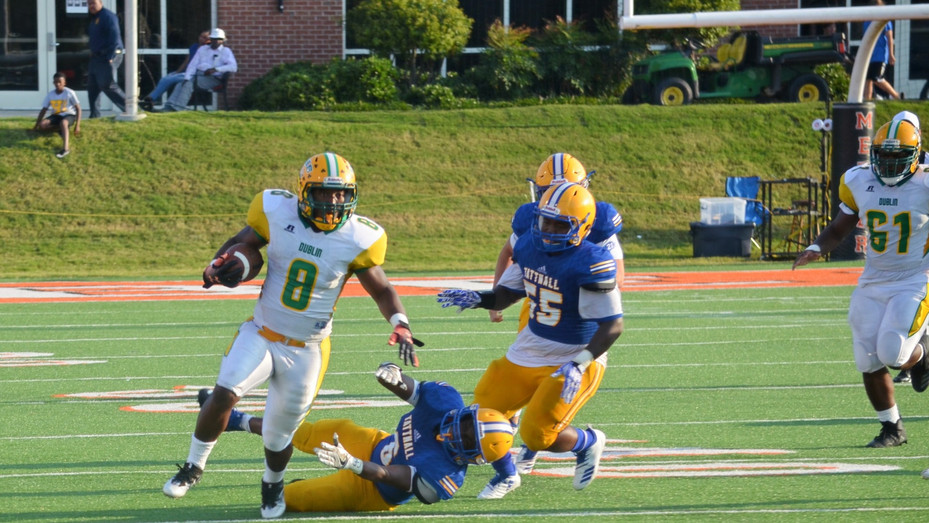 Dublin's Corteveyas Mitchell deposits a cluster of Tattnall Square defenders as he rumbles for a long rushing touchdown in the 2018 Macon Touchdown Club Kickoff Classic.