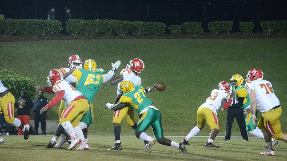 Dublin defensive linemen Khalil White (63) and Steve Linton (27) knock the ball from the hand of Thomasville quarterback Chad Mascoe, forcing a key turnover early in their 2018 second-round playoff win in The Shamrock Bowl. The hard-hitting pass rush of the Irish helped shut down the high-producing Bulldogs and secure their first berth in the state football quarterfinals since 2011.