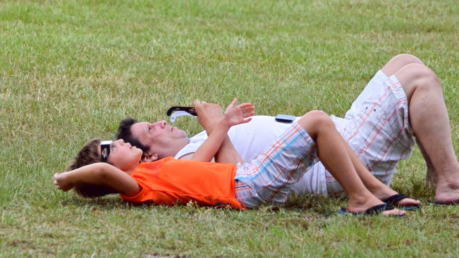 A father and son lounge in the grass at Fairview Park waiting for clouds to clear and their chance to view the August 21, 2017 solar eclipse through special protective glasses.