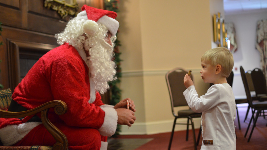 Timothy Redding offers a cookie to Santa Claus during a visit several days prior to Christmas at a meeting of the Dublin Rotary Club in 2017.