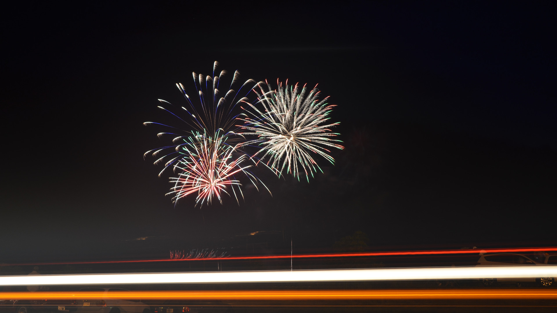 Traffic passes by on Ga. 257 while fireworks explode in the distance above the Dublin Civitan Fairgrounds during a 2018 Fourth of July celebration.