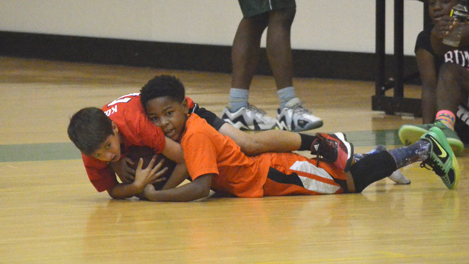 Two campers dive after a loose ball during a scrimmage game at Dublin High School's annual youth basketball summer camp.
