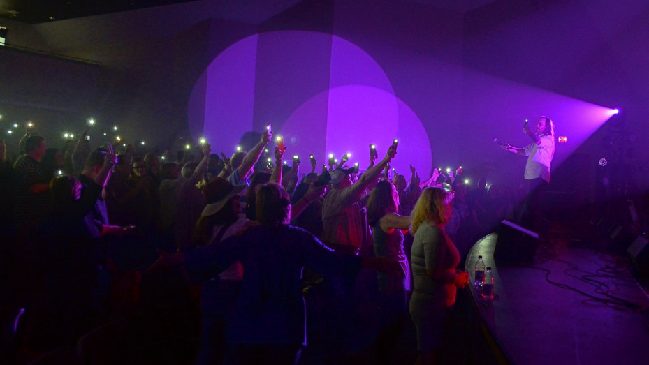 """Audience members at Theatre Dublin follow along with lead singer Brian Williams, of Journey tribute band """"Departure,"""" in waving their shining cell phone flashlights during a rendition of the band's hit """"Faithfully"""" at a benefit concert in 2017."""