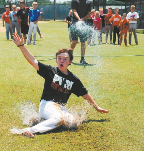 Grant Grosch and fellow campers cool off with some water fun while also working on their sliding technique during a drill in a 2013 baseball summer camp.