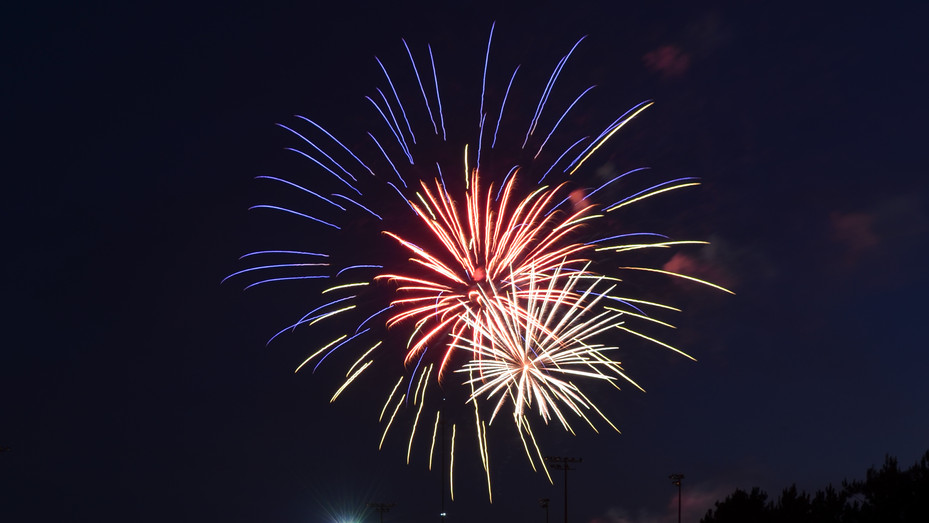 A trio of red, white and blue fireworks burst above Southern Pines Regional Park, leaving a glittering reflection over a nearby pond and water feature, during a Fourth of July celebration in 2017.