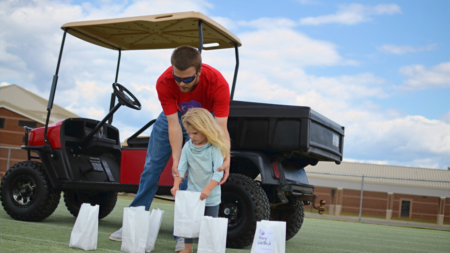 Kyle Outlaw assists a young helper in placing luminaries in honor or memory of those having battled cancer around the Dublin High School track before Dublin-Laurens County's 2016 Relay for Life.