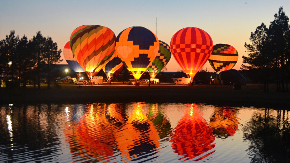 A group of glowing hot air balloons create a majestic light show against the sunset above Southern Pines Regional Park during the 2018 Irish Balloon Festival.