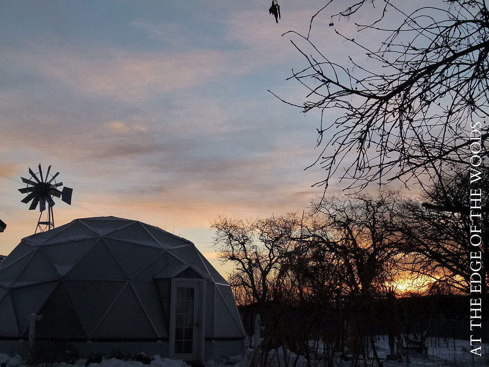 the sun rises behind the greenhouse growing dome