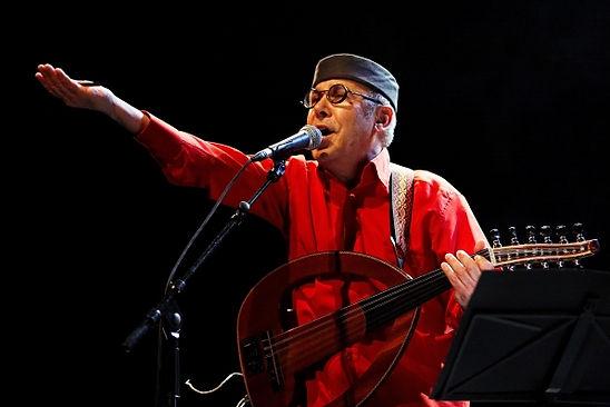 Photo prise lors d'un concert de radio bagdad en 2012. On y voit Fawzy tendant la paume de sa main ouverte vers son public et toujours accompagné de son oud électrique.