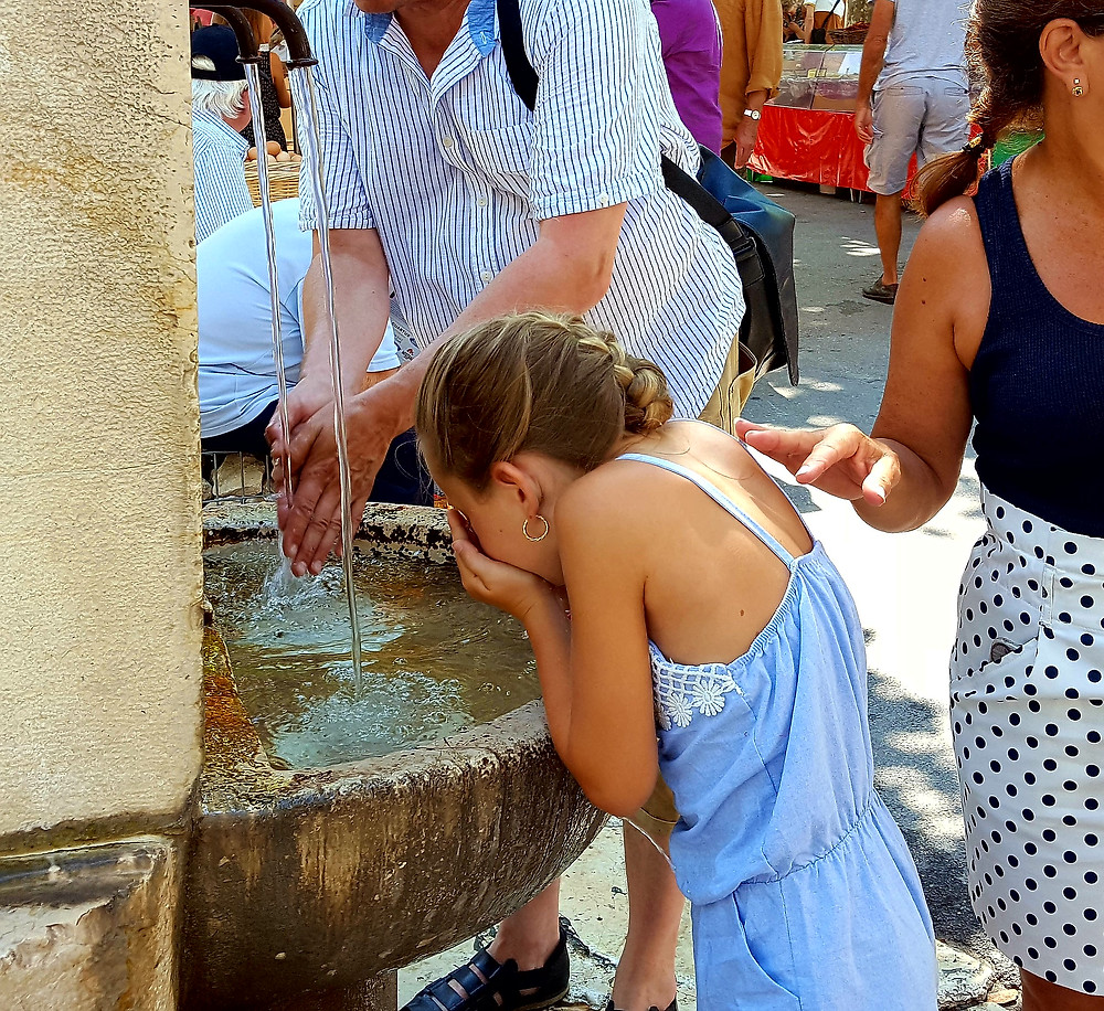 Mom & daughter refresh themselves at the spring water fountain