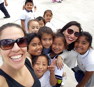 Women smiling with kids at schol