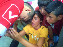 Sarah showing Syrian boys how to use Snapchat