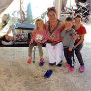 Latifa with spirited Yazidi children and their exhausted mother