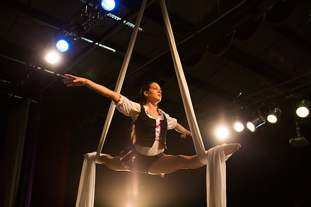 circus school high school student is balancing on an aerial silk during a performance