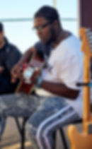 Male student playing guitar outside at music school