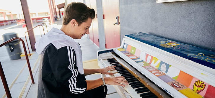 teenage boy playing a piano outdoors at a music high school