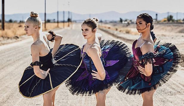 dance school three prima ballerinas pose in costume designed platter tutus in the desert