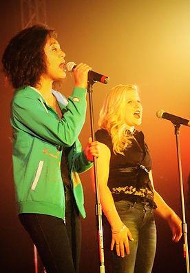 Singing High School students perform onstage as pop singers