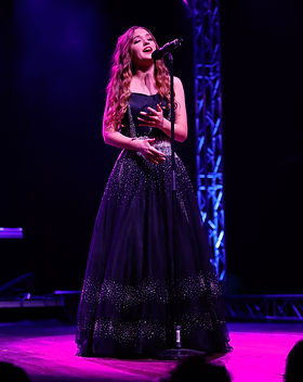 high school female opera singer sings onstage from music school