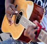 high school music school male plays acoustic guitar