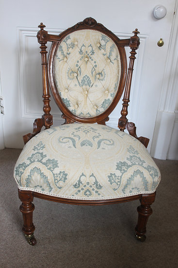 A fine solid walnut Victorian carved ladies or nursing chair.