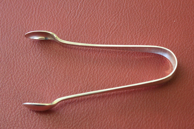 A small pair of hallmarked silver sugar tongs