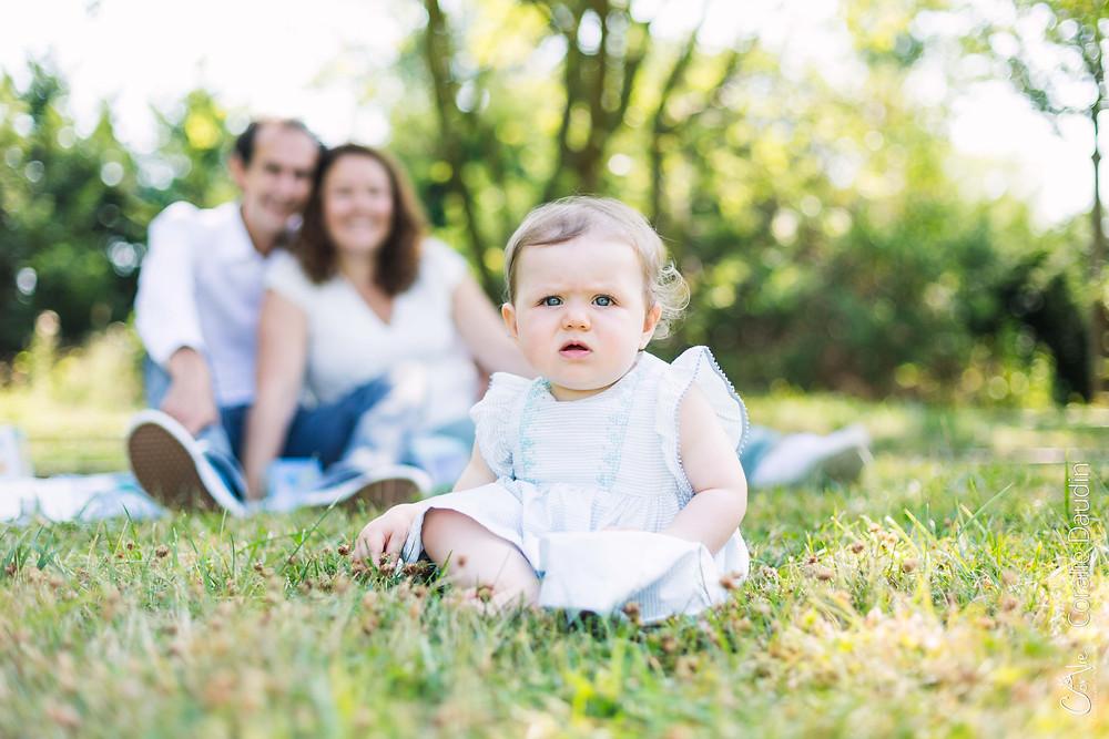 portrait bébé dans l'herbe devant ses parents