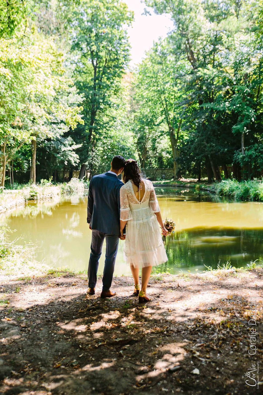 photo couple de mariés de dos devant un bassin