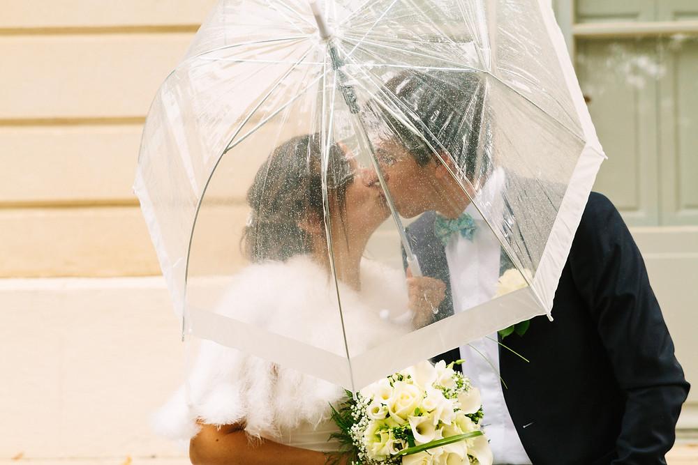 Mariés sous la pluie avec leur parapluie