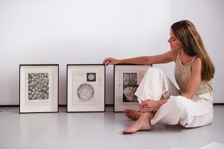 Fotografía de Pilsferrer sentada en el suelo con 3 de sus diseños