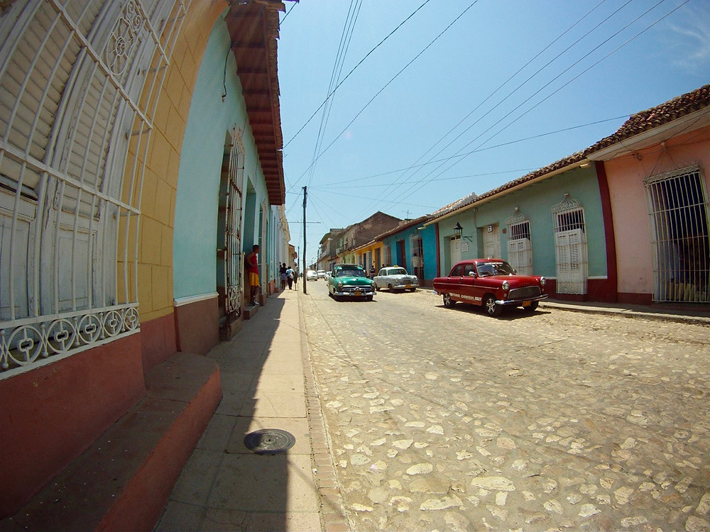 Street view of old buildings and cars in Trinidad in Cuba
