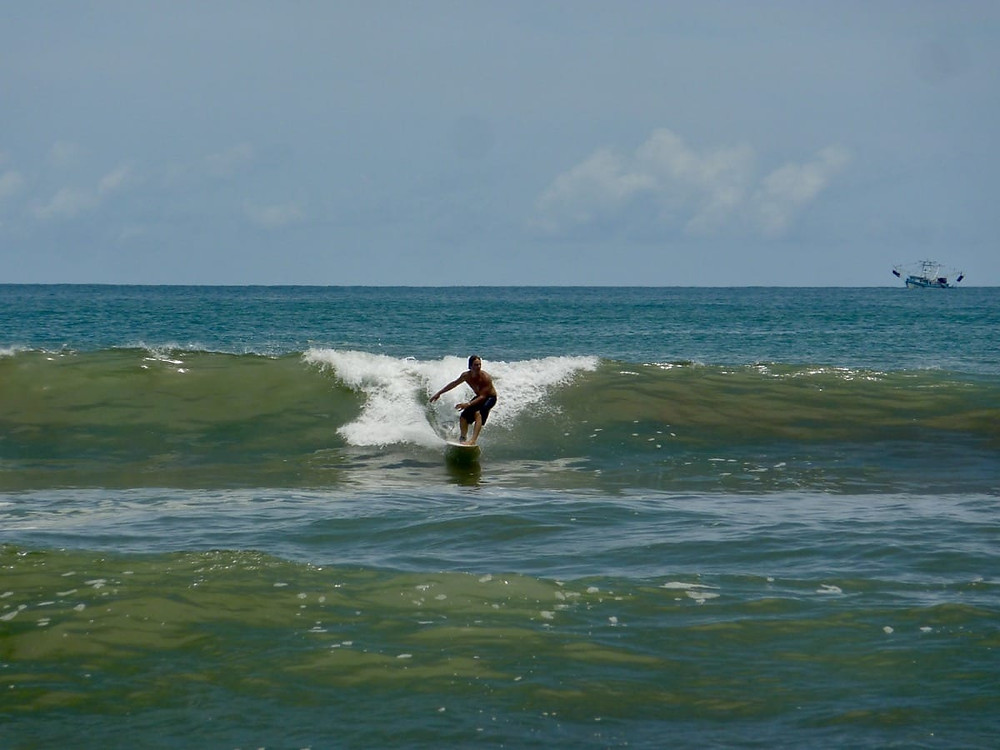 Ollie surfing a small wave at Dominical in Costa Rica
