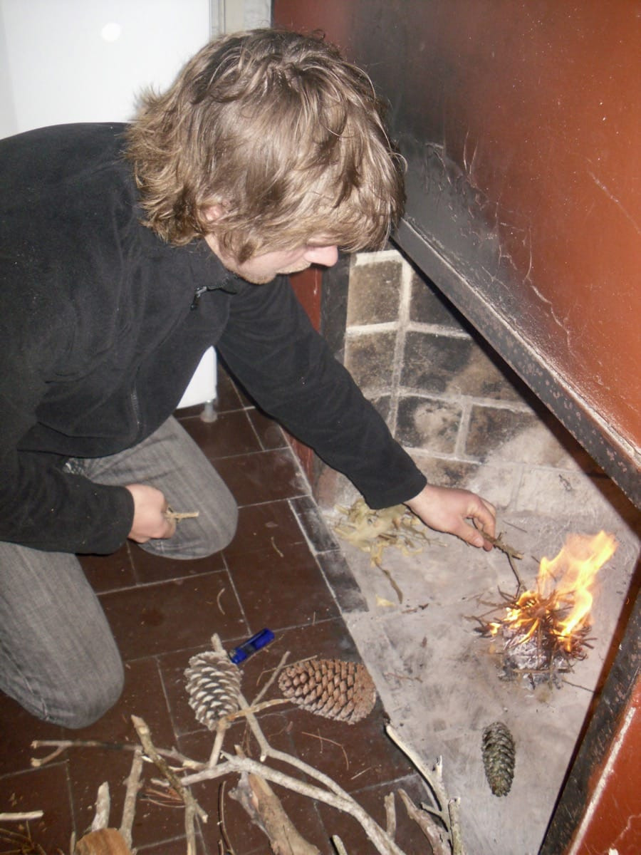 Ollie lighting an open fire in our cosy cabin in Punta del Diablo, Uruguay
