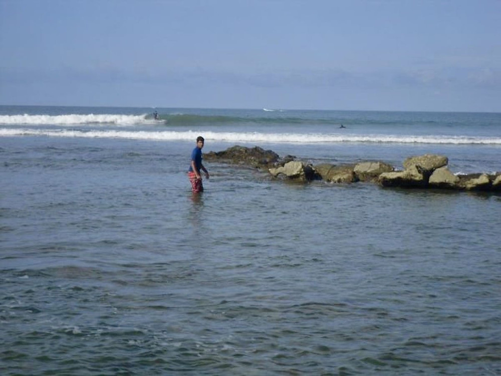 Ollie surfing the shallow reef of San Mateo in Ecuador