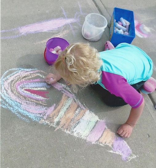 Girl drawing with chalk on sidewalk