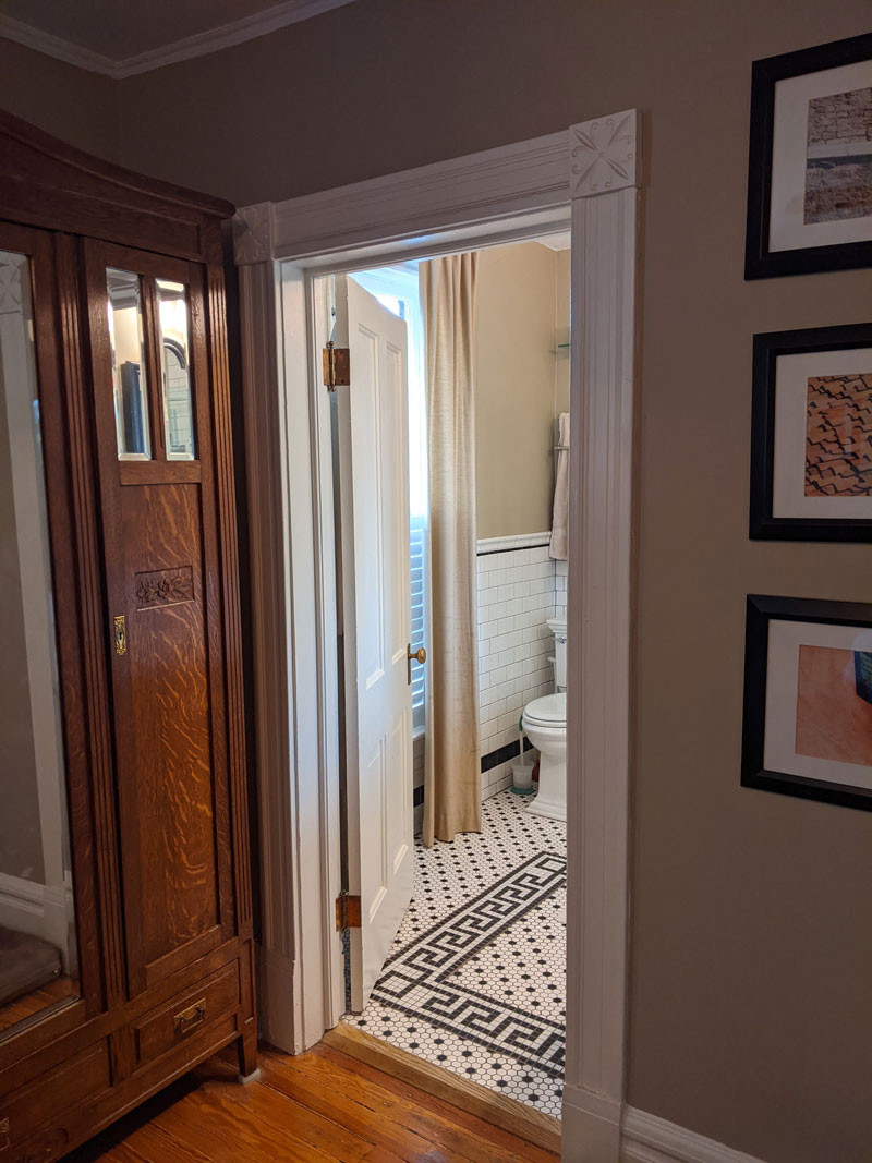 Finished Doorway to a Master Bathroom with Original Trim and Rosettes