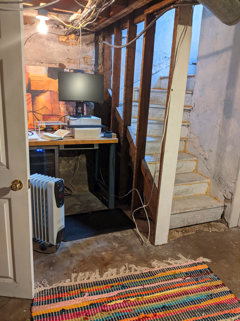 Adding character to an unfinished basement home office with a colorful rug and painting