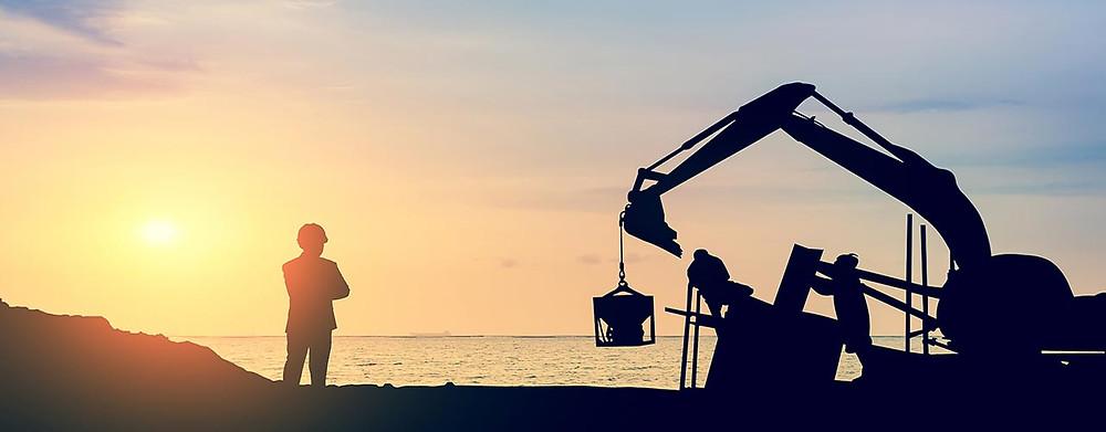 Pelle industrielle creusant un trou au crépuscule, avec un homme qui regarde