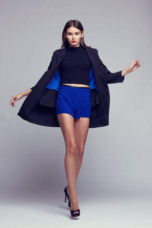 Lookbook fahsion photography in Dubai: Girl with stunning hair and makeup poses in a stylish pair of blue shorts.