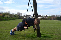 Client using suspension training equipment during an outdoor session