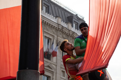 Two men climb atop a lightpost