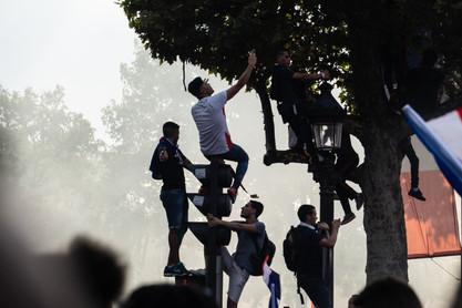 Parisians climb lightposts to watch the celebrating crowds